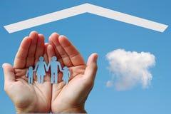 Famille de papier dans des mains avec la maison sur le fond de ciel bleu Photo stock