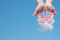 Famille de papier dans des mains sur le concept d'assistance sociale de fond de ciel bleu Photos stock