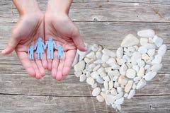 Famille de papier dans des mains sur le fond en bois avec le coeur en pierre blanc Photos libres de droits