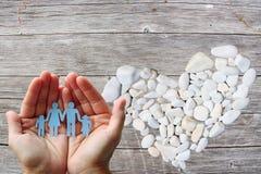Famille de papier dans des mains sur le fond en bois avec le coeur en pierre blanc Image stock