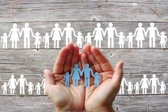 Famille de papier dans des mains sur le fond en bois avec les familles blanches Photographie stock libre de droits