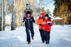 Famille de quatre appréciant en parc d'hiver Images stock