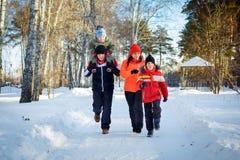 Famille de quatre appréciant en parc d'hiver Images libres de droits