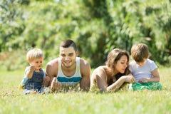 Famille de quatre dans l'herbe au parc Photos libres de droits