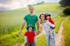 Famille de quatre dans le domaine sur un chemin rural, printemps, ayant l'amusement Images libres de droits
