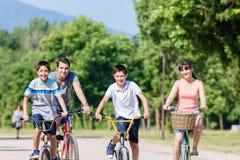 Famille de quatre en tournée de vélo en été Image stock
