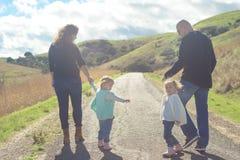 Famille de quatre heureuse augmentant en parc avec la belle vue Photo libre de droits