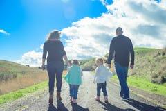 Famille de quatre heureuse augmentant en parc avec la belle vue Photographie stock libre de droits