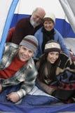 Famille de quatre heureuse détendant dans la tente Photos stock