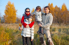 Famille de quatre heureuse en stationnement d'automne Images stock