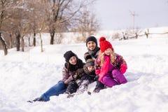 Famille de quatre heureuse se reposant dans la forêt de neige Images libres de droits