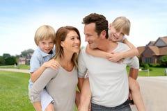 Famille de quatre heureuse se tenant dans le voisinage dehors Images stock