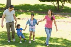 Famille de quatre mains se tenantes et de la marche au parc images stock