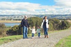 Famille de quatre marchant sur la belle traînée dans les collines Photos libres de droits