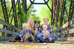 Famille de quatre personnes et de chien se reposant sur le pont en automne Images libres de droits