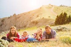 Famille de quatre personnes regardant au beau paysage marin en montagnes image libre de droits