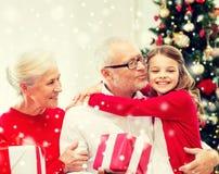 Famille de sourire avec des cadeaux à la maison image libre de droits