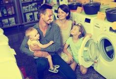 Famille de sourire avec des enfants choisissant la machine à laver Photos stock