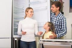 Famille de sourire avec l'enfant choisissant le réfrigérateur Image stock