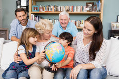 Famille de sourire avec le globe tout en se reposant sur le sofa Images stock