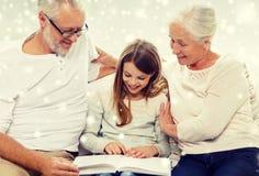 Famille de sourire avec le livre à la maison Image libre de droits