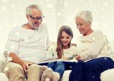 Famille de sourire avec le livre à la maison Image stock