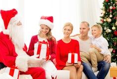 Famille de sourire avec le père noël et des cadeaux à la maison Photo libre de droits