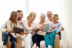 Famille de sourire avec le PC de comprimé à la maison image libre de droits
