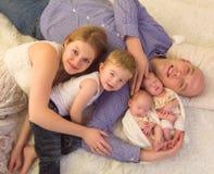 Famille de sourire avec les jumeaux nouveau-nés photos stock