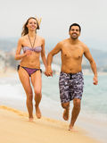 Famille de sourire courant sur la plage d'océan Image libre de droits