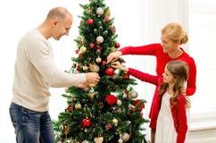 Famille de sourire décorant l'arbre de Noël à la maison Image libre de droits