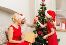 Famille de sourire décorant l'arbre de Noël Image libre de droits