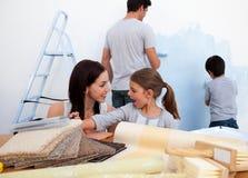 Famille de sourire décorant leur maison neuve Images libres de droits