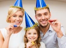 Famille de sourire dans des chapeaux bleus soufflant des klaxons de faveur photographie stock