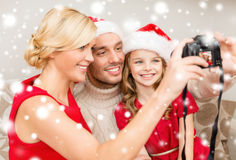 Famille de sourire dans des chapeaux d'aide de Santa prenant la photo Photo stock