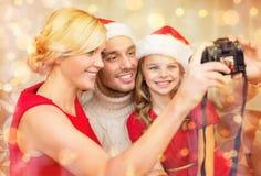 Famille de sourire dans des chapeaux d'aide de Santa prenant la photo Photos libres de droits