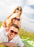 Famille de sourire dans des lunettes de soleil se trouvant sur la couverture images stock