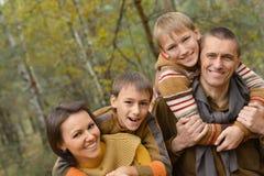 Famille de sourire dans la forêt d'automne Photographie stock libre de droits
