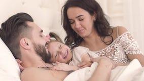 Famille de sourire dans le lit où la jeune mère réveille sa petite fille avec un baiser banque de vidéos