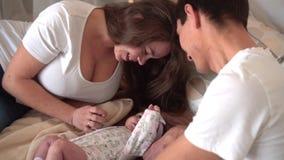 Famille de sourire dans le lit o? le papa et la maman sont observants, touchant et parlant avec leur fille de b?b? banque de vidéos