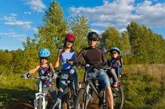 Famille de sourire faisant un cycle à l'extérieur Photos stock