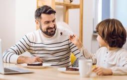 Famille de sourire heureuse mangeant ensemble Photo stock