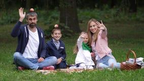 Famille de sourire heureuse ondulant dans la caméra en parc d'automne Papa, maman, fille, fils 4K Mouvement lent banque de vidéos