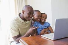Famille de sourire heureuse utilisant l'ordinateur portable Image stock