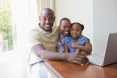 Famille de sourire heureuse utilisant l'ordinateur portable photographie stock libre de droits