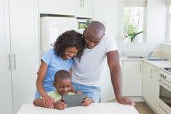 Famille de sourire heureuse utilisant le comprimé numérique photos libres de droits