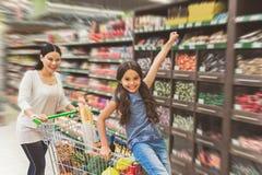 Famille de sourire joyeuse ayant l'amusement dans le supermarché photos libres de droits