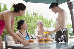 Famille de sourire mangeant des hamburgers par la piscine des vacances Image libre de droits