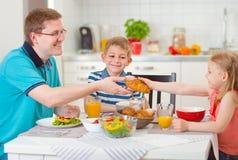Famille de sourire mangeant le petit déjeuner dans la cuisine Photo libre de droits