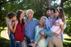 Famille de sourire posant ensemble en parc Photo stock